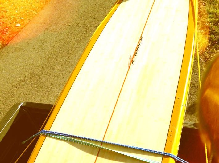 paddle board strapped in back of truck