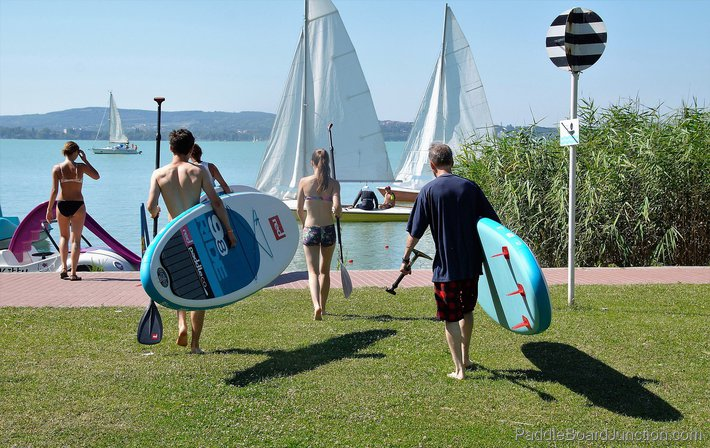 People Carrying Stand Up Paddle Boards