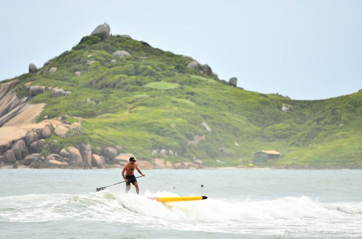 surfing on paddle board, green mountain in bacground