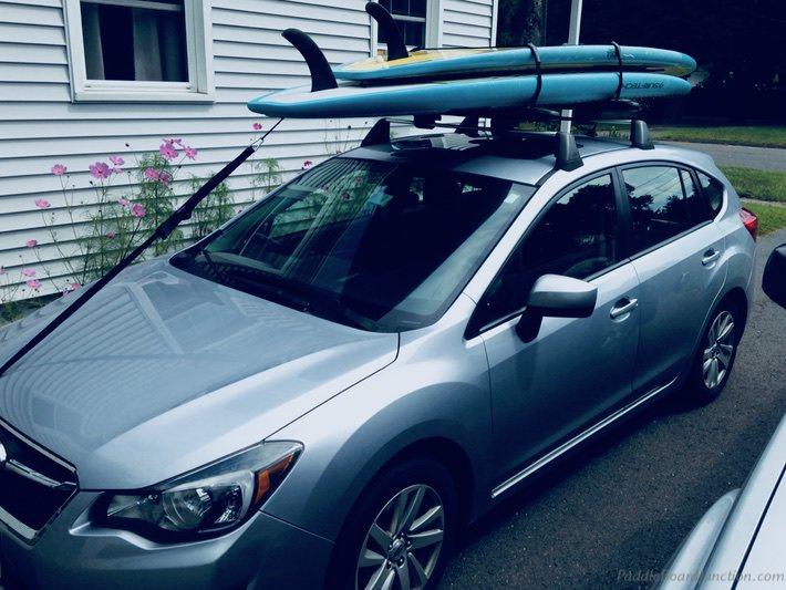 two paddle boards on a car's roof rack